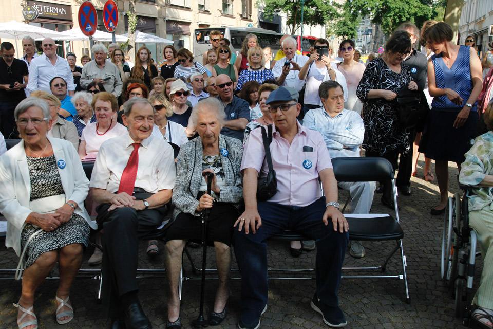ältere Menschen sitzen auf Stühlen im Freien
