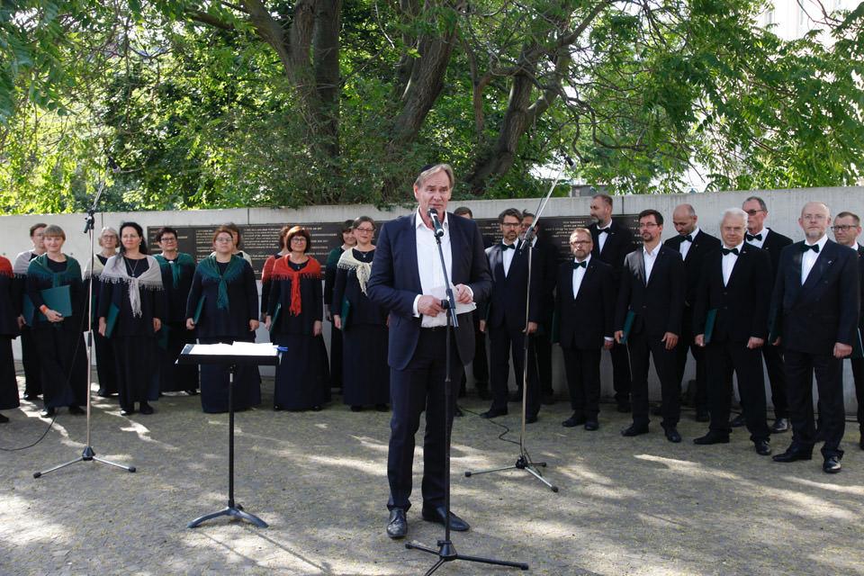 Oberbürgermeister Jung hält eine Rede, dahinter steht der Leipziger Synagogalchor