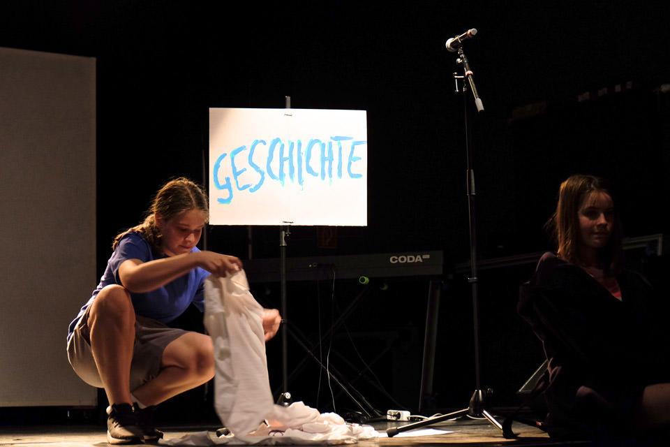 Junger Mann hockt auf einer Bühne, im Hintergrund ein Schild mit dem Titel Geschichte