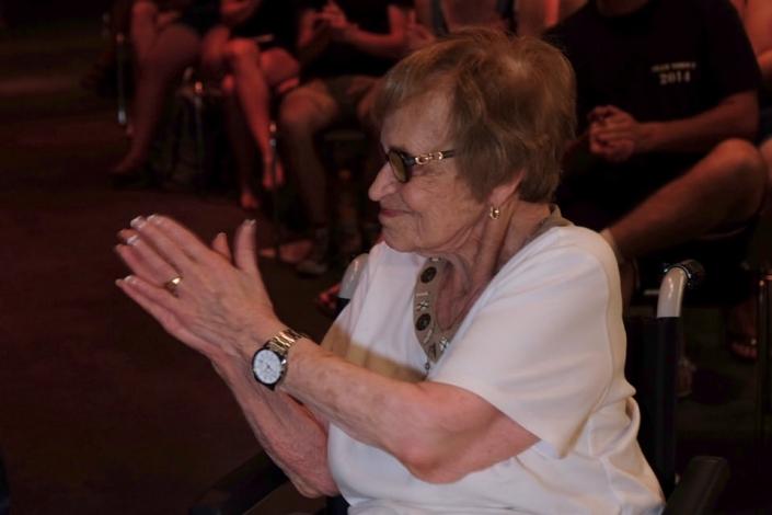 Alte Frau applaudiert im Sitzen