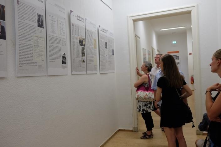 Menschen in einer Ausstellung schauen auf Schrifttafeln